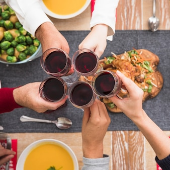 People clanging wine glasses above festive table