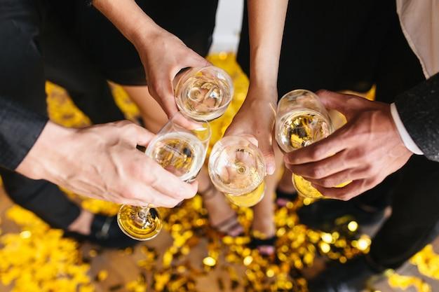人々はシャンパンでいっぱいのグラスをチリンと鳴らします