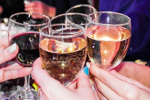人々はグラスを赤と白のワインでチリンと鳴らします。女性の手にワインのグラス、女性のアルコール依存症、女性の休日