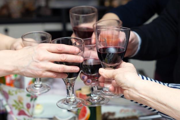 自宅のお祝いテーブルでグラスをチリンと鳴らす人々