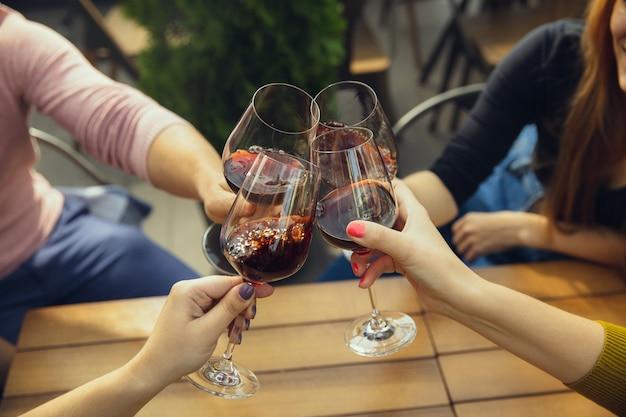 카페나 레스토랑의 여름 테라스에서 와인과 함께 안경을 부딪치는 사람들. 행복하고 쾌활한 친구들은 여름이나 가을 축제를 축하합니다. 인간의 손, 라이프 스타일의 총을 닫습니다.