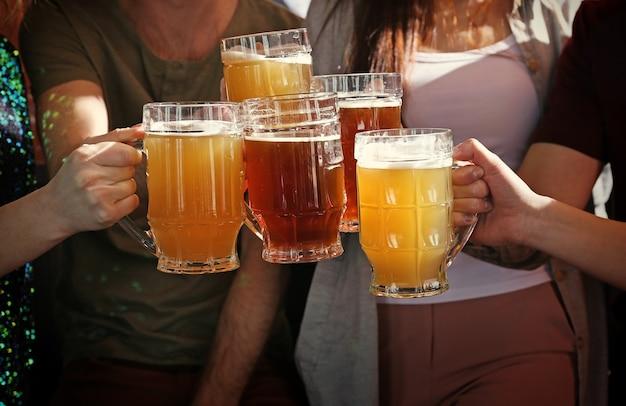 술집, 근접 촬영에서 맥주와 함께 머그잔을 부딪 치는 사람들