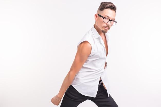 人、服、スタイルのコンセプト-コピースペースと白い背景の上の白いシャツでポーズをとる若いセクシーなハンサムな男