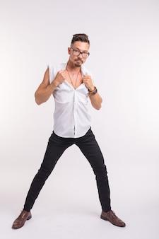 Люди, одежда и концепция стиля - молодой сексуальный красивый мужчина позирует в белой рубашке на белом фоне