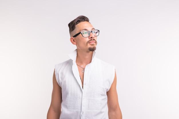 人、服、スタイルのコンセプト-白い背景の上の白いシャツでポーズをとって若いセクシーなハンサムな男