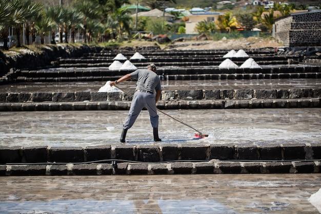 사람들은 모리셔스의 인도양 해안에서 맑은 날에 소금을 수집합니다.
