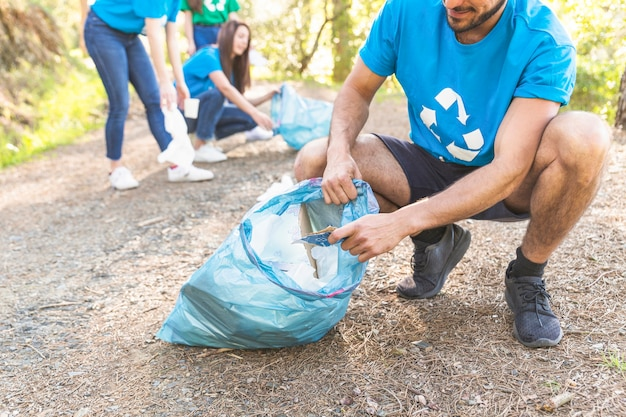 People collecting trash in forest