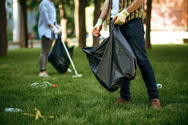 People collects garbage in a bag in park, volunteering. male person cleans forest, ecological restoration, eco lifestyle, trash collection and recycling, ecology care, environment cleaning