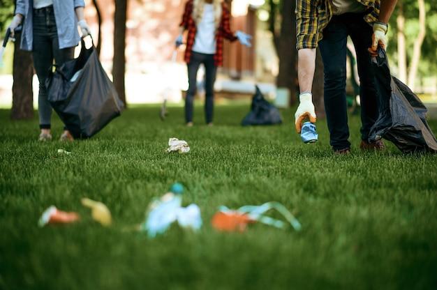 Люди собирают пластиковый мусор в мешки в парке, занимаются волонтерством