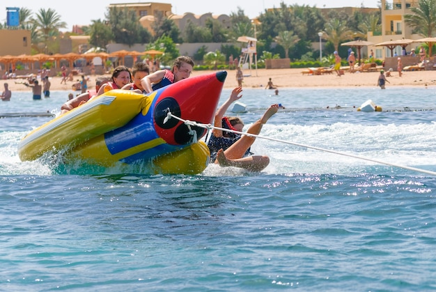 People on colorful banana boat floating on the water with splashing water