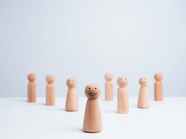 사람들이 커뮤니티 개념입니다. 복사 공간이 있는 흰색 배경에 함께 서 있는 행복한 미소를 지닌 남성과 여성의 나무 인물 그룹.