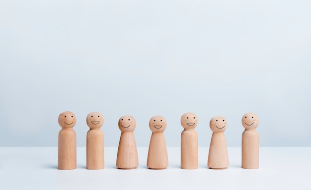 People community concept. group of wooden figures, male and female with happy smile faces standing together on white background with copy space.