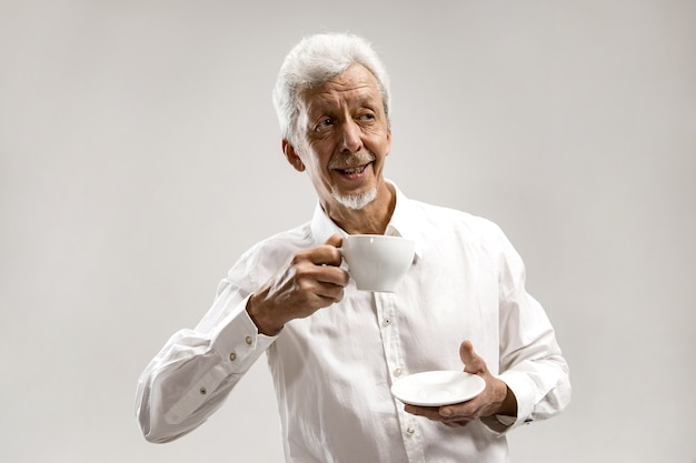 People concept - happy senior man with cup of tea at studio. human emotions concept