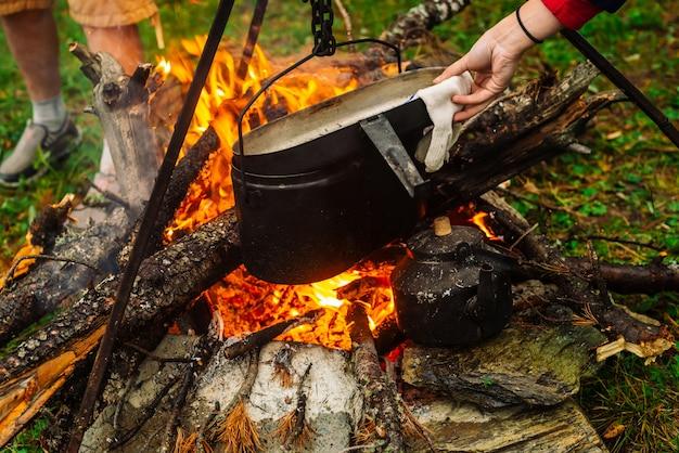 Люди готовят еду на открытом воздухе.