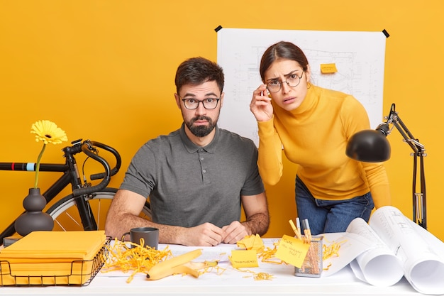 People cooperation occupation job concept. puzzled surprised hard working woman and man coworkers pose at desktop with papers excited about final result draw sketches during working day in office