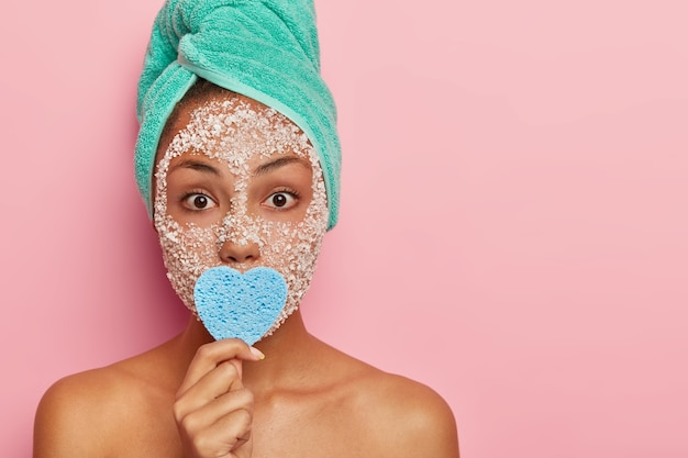 People, cosmetology and wellness concept. indoor shot of surprised young female model stands naked indoor, covers mouth with blue heart shaped cosmetic sponge, wears facial beauty mask for purity