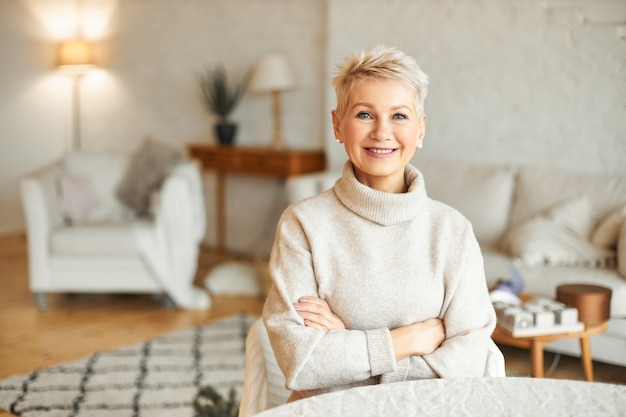 People, coziness, domesticity and season concept. charming beautiful retired woman spending leisure time indoors at home with confident smile, keeping arms folded on her chest