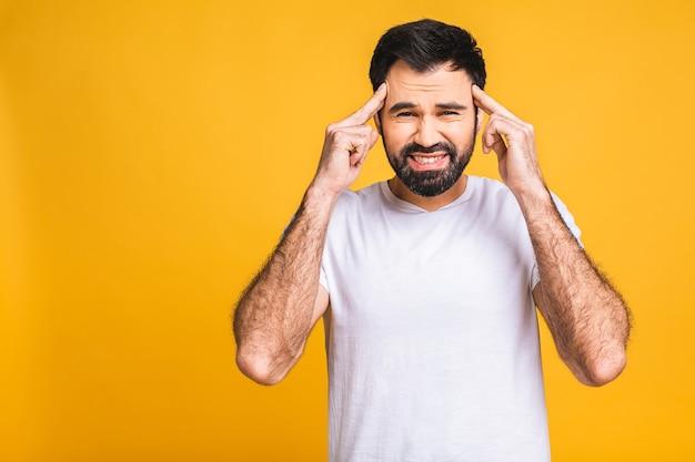 人々、危機、感情、ストレスの概念-自宅で頭痛に苦しんでいる不幸な疲れた男。黄色の背景の上に分離されました。
