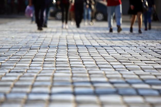 人々はぼやけた焦点で歩道を横断する歩行者で道路を横断します