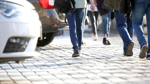 Люди переходят дорогу перед машиной. транспорт и пешеходные дорожки