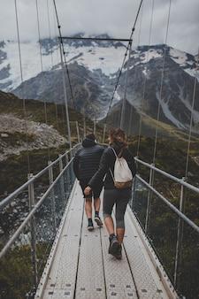 ニュージーランドのマウントクックで橋を渡る人々