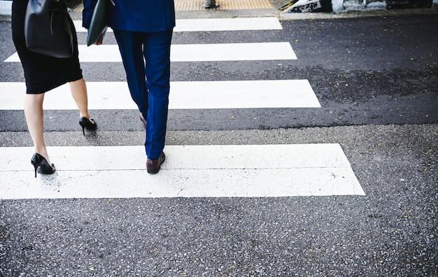 Люди, пересекающие городскую дорогу
