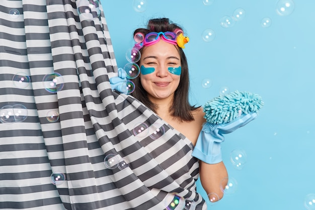 People daily routine and hygiene concept. positive sincere asian woman enjoys cleansing body and exfoliating skin holds sponge makes curly hairstyle poses against blue background balloons around.