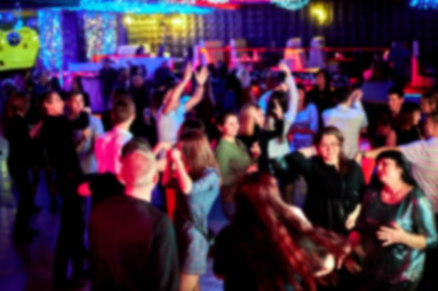 사람들은 나이트 클럽의 댄스 플로어에서 춤을 춥니 다. 밝은 스트로브 조명. 초점이없고 배경이 흐릿합니다.
