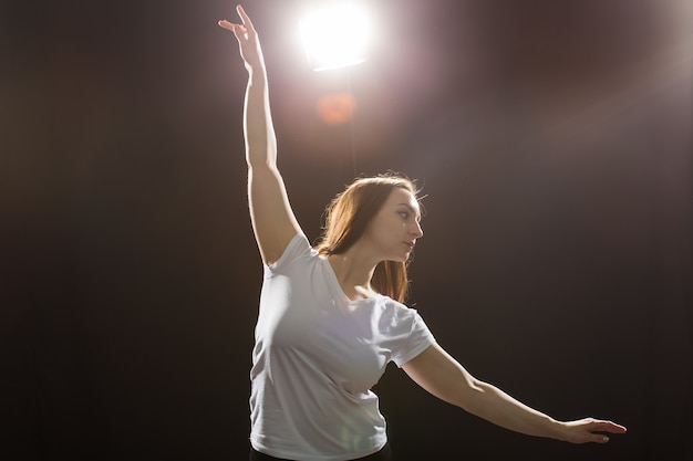 People and dancing concept - young beautiful sporty woman dancing jazz funk on a black studio background.