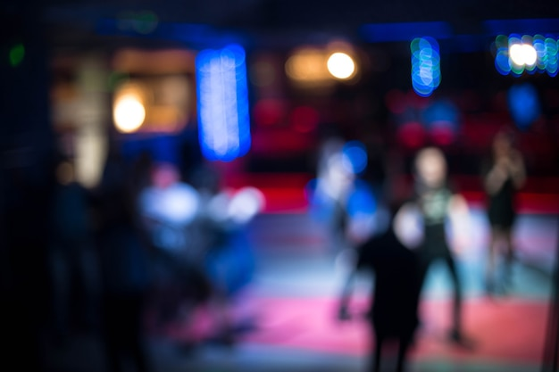 People dancing having fun and relax in a night club blurred background. beautiful blurry lights on the dance floor