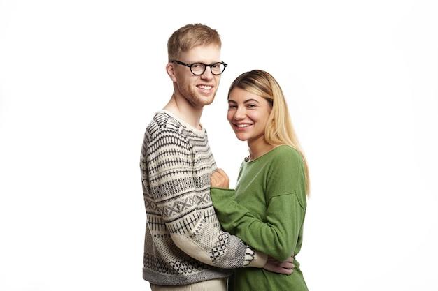 Persone, incontri, amore, romanticismo e concetto di solidarietà. ritagliata colpo di bella giovane uomo barbuto in occhiali alla moda che tiene affascinante femmina per la vita, sia ridendo che guardando