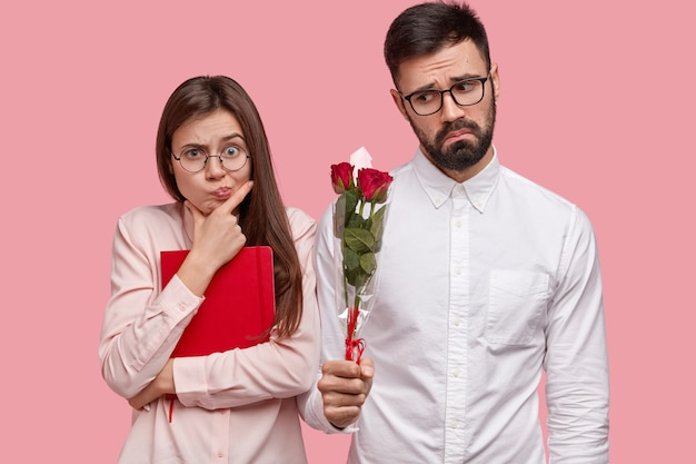 People, dating and relationship concept. displeased bearded man in white elegant shirt gives girlfriend roses, wants to apology