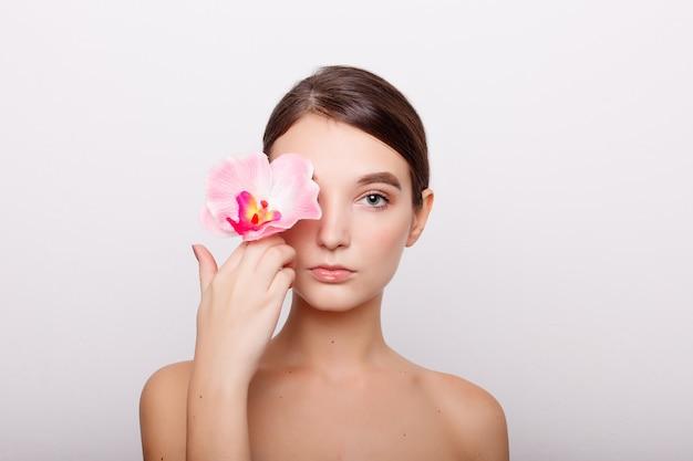 사람, 탈수, 스킨 케어 및 뷰티 개념-난초 flowers.beauty 모델 여자 얼굴을 가진 아름 다운 소녀입니다. 완벽한 피부. 전문 메이크업. 피부에 아름 다운 여자 얼굴 근접 촬영 초상화 손