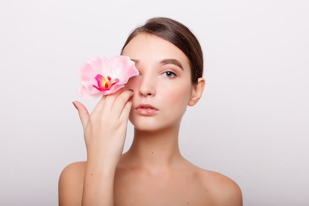 People, dehydration, skincare and beauty concept - beautiful girl with orchid flowers.beauty model woman face. perfect skin. professional make-up. beautiful woman face closeup portrait hands on skin