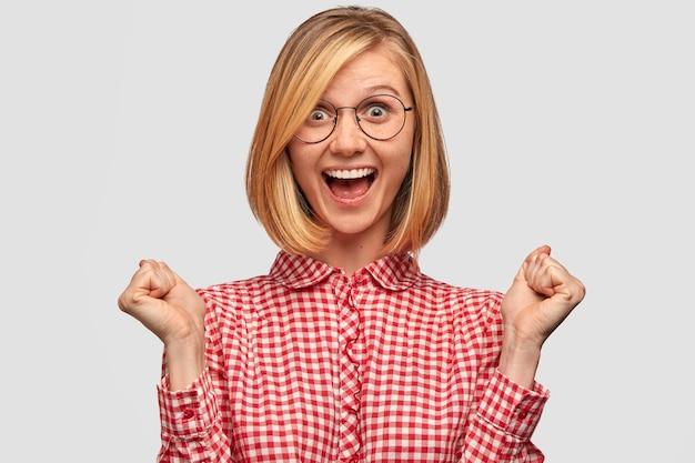Концепция определения и достижения людей. радостная женщина с модной прической аплодирует, празднует успех, сжимает кулаки и восклицает да, одетая в модную элегантную рубашку, изолирована на белой стене