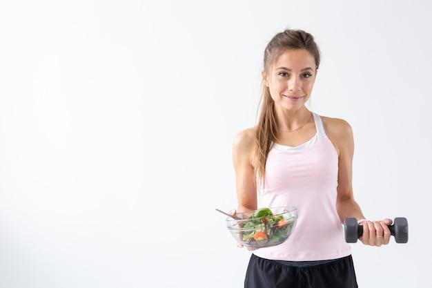사람, 다이어트와 건강 한 라이프 스타일 개념-복사 공간 흰색 배경 위에 샐러드와 아령 여자의 초상화.