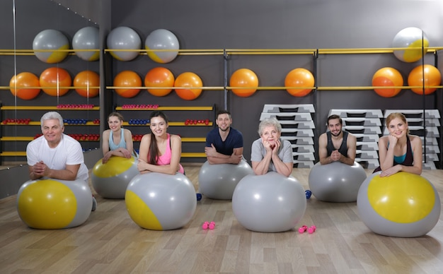 People of different ages training with fit balls in gym