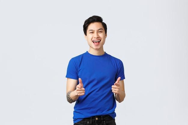 人々のさまざまな感情、ライフスタイル、カジュアルなコンセプト。青いtシャツ、指を上に向ける、落とし穴のジェスチャー、大きな勝利、灰色の背景を持つ人を祝福する陽気な明るいアジア人