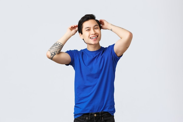People different emotions, lifestyle and casual concept. carefree good-looking asian guy happy visited barbershop, touching brand new haircut, smiling pleased, standing grey background.