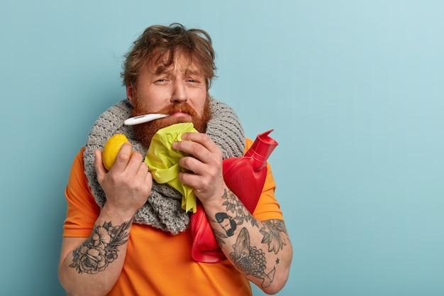 사람, 질병, 의료 및 인플루엔자 개념. 낙담 한 빨간 머리 수염 난 남자는 체온이 높고, 기분이 좋지 않으며, 티슈, 뜨거운 병 및 레몬을 들고 집에서 질병을 치료합니다.