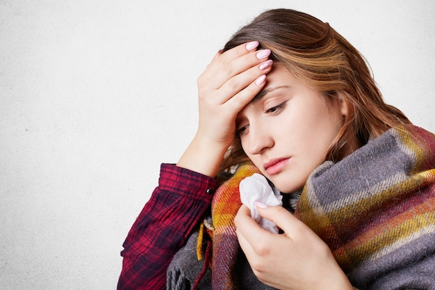 People, disease, healthcare concept. stressful woman has flu, suffers from running nose, bad cold and headache, wrapped in wool plaid, looks down, isolated over white wall with copy space