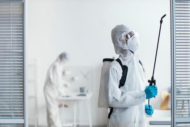Persone che disinfettano insieme un'area pericolosa