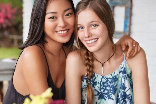 人、多様性、異人種間の友情の概念。 2人の美しい混血女性がカフェテリアで一緒に再現するときに抱き合う
