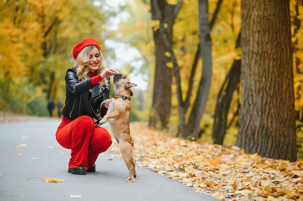People and dogs outdoors. beautiful and happy woman enjoying in autumn park walking with her adorable french bulldog.