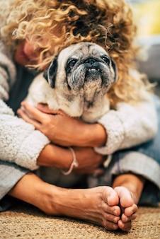 人々の犬の飼い主と親友はコンセプトが大好きです-女性は床に座って家で彼女のパグを抱きしめます-子犬の保護と友情療法