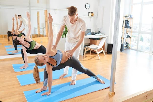 Люди, делающие расширенный треугольник, позируют в классе йоги