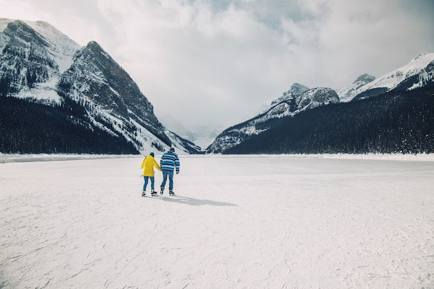 Люди катаются на коньках на замерзшем озере луиза в банфе