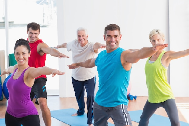 People doing warrior pose in yoga class