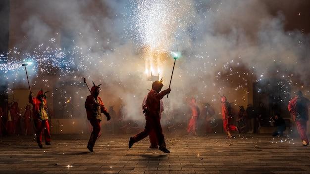 Люди, одетые как дьяволы, танцующие с пиротехникой