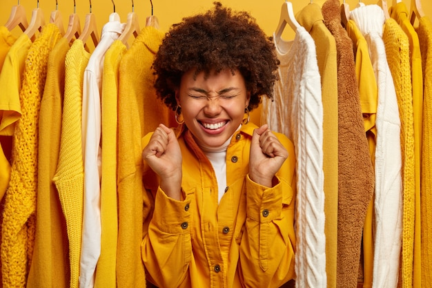Persone, vestirsi, concetto di acquisto. felice donna dalla pelle scura con un sorriso a trentadue denti, stringe i pugni, sta in piedi nel guardaroba tra i vestiti